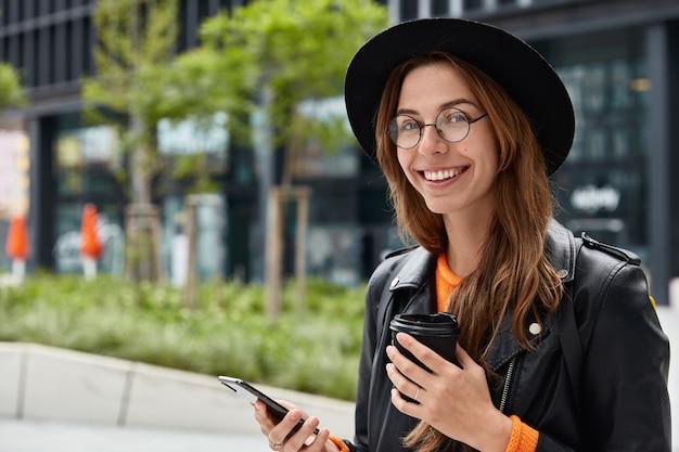 Tevreden blanke vrouw controleert rekeningsaldo of surft op sociale netwerken, drinkt koffie om te gaan Gratis Foto