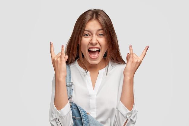 Tevreden dolblij jonge brunette vrouw toont rock gebaar, proost en viert iets Gratis Foto