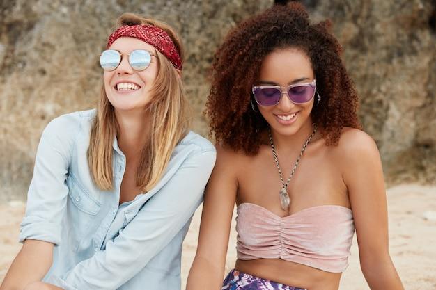 Tevreden europese vrouw in trendy tinten, draagt een hoofdband, kijkt naar de felle zon aan de hemel, zit naast haar afro-amerikaanse vriend, heeft echte vriendschap, zit tegen een klif of berg Gratis Foto