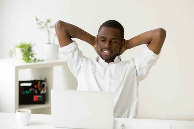 Tevreden gelukkig afro-amerikaanse man ontspannen met koffie en laptop Gratis Foto