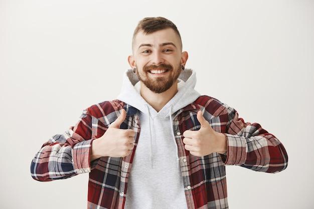 Tevreden gelukkig glimlachende man die duimen toont, goed werk prijst, goed gedaan Gratis Foto