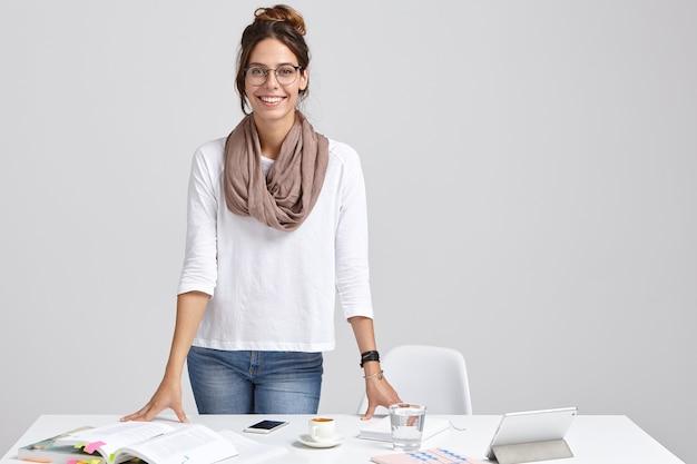 Tevreden intelligente vrouwelijke docent draagt een witte trui en spijkerbroek Gratis Foto