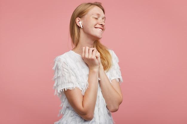 Tevreden jonge aantrekkelijke vrouw met foxyhaar opgeheven handen vouwen en positief glimlachen terwijl ze luistert naar haar favoriete muzieknummer, staande tegen een roze achtergrond Gratis Foto
