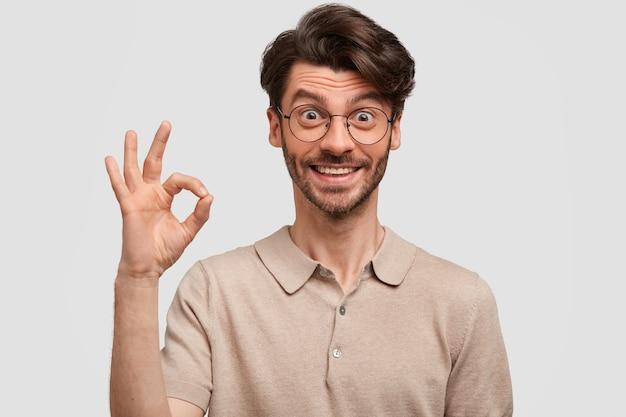 Tevreden jonge bebaarde hipster toont ok teken, toont zijn instemming, bewijst dat alles geweldig is Gratis Foto