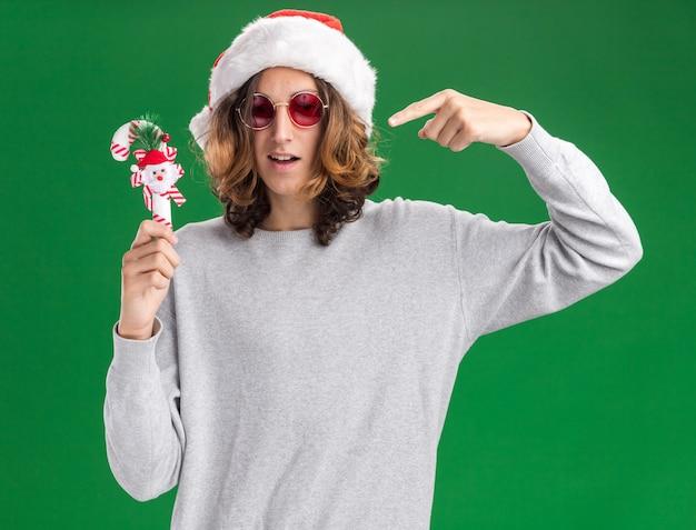 Tevreden jonge man met kerst kerstmuts en rode bril met kerst candy cane glimlachend wijzend witn wijsvinger op het staande over groene achtergrond Gratis Foto