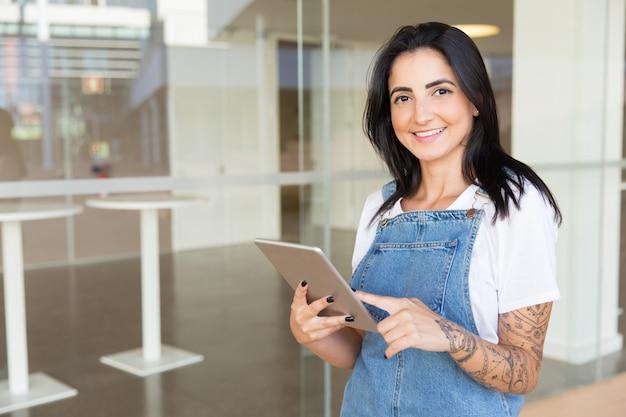 Tevreden jonge vrouw die digitale tablet houdt Gratis Foto
