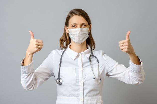 Tevreden jonge vrouwelijke arts die duim op geïsoleerd gebaar toont Premium Foto