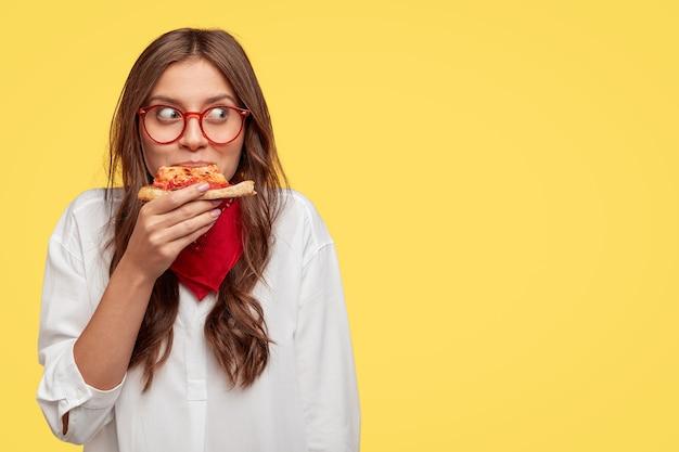 Tevreden kaukasisch model eet heerlijke pizza binnen, heeft lunch, draagt optische bril, wit overhemd en rode bandana, staat tegen gele muur met vrije ruimte voor uw slogan of tekst Gratis Foto