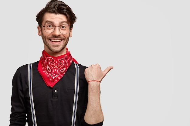 Tevreden knappe man in modieuze kleding, blij om je richting te wijzen, wijst met duim opzij, heeft een vrolijke gezichtsuitdrukking en een charmante glimlach Gratis Foto