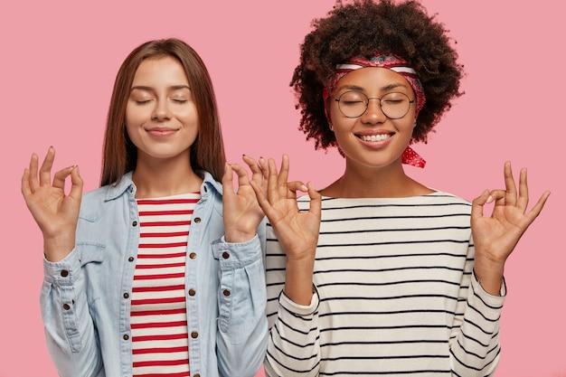 Tevreden maken twee vrouwen van verschillend ras een goed gebaar met beide handen, sluiten de ogen, proberen zich te concentreren Gratis Foto