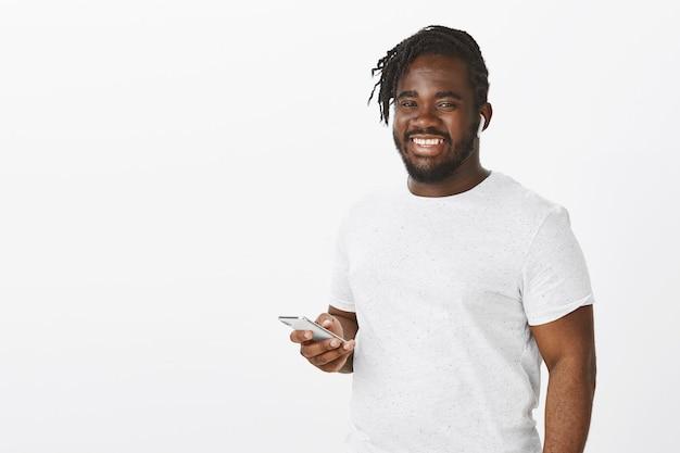 Tevreden man met vlechten poseren tegen de witte muur met zijn telefoon Gratis Foto