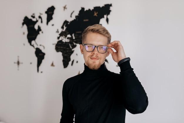 Tevreden man met werk. gelukkig jonge man aan het werk op laptop terwijl poseren op zijn werkplek op kantoor. Gratis Foto