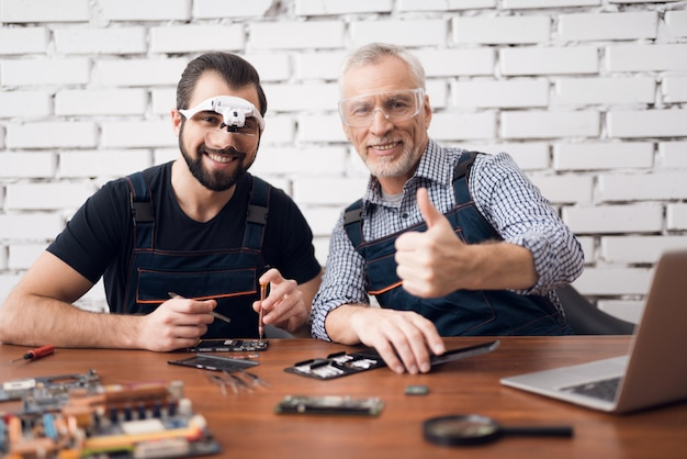 Tevreden mannen testen laptopcomponenten gadget repareren. Premium Foto