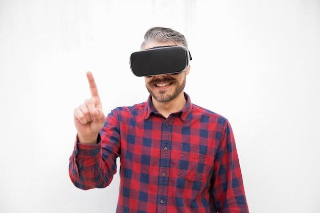 Tevreden mens die in vr-hoofdtelefoon met vinger richten Gratis Foto
