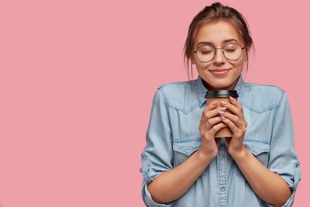 Tevreden mooie blanke vrouw houdt aromatische drank vast, drinkt cappuccino of koffie, voelt warm aan, sluit de ogen van plezier Gratis Foto
