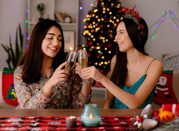 Tevreden mooie jonge meisjes gerinkel glazen champagne aan tafel zitten en genieten van kersttijd thuis Gratis Foto