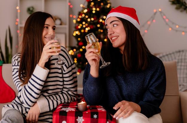 Tevreden mooie jonge meisjes houden glazen champagne en kijken elkaar zittend op fauteuils en genieten van kersttijd thuis Gratis Foto