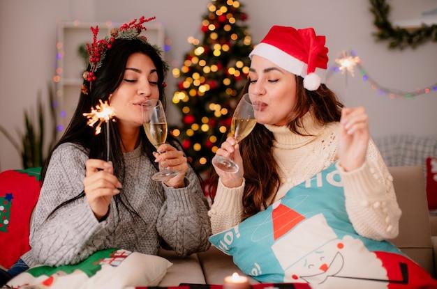 Tevreden mooie jonge meisjes met kerstmuts drinken glazen champagne en houden wonderkaarsen zittend op fauteuils en genieten van kersttijd thuis Gratis Foto