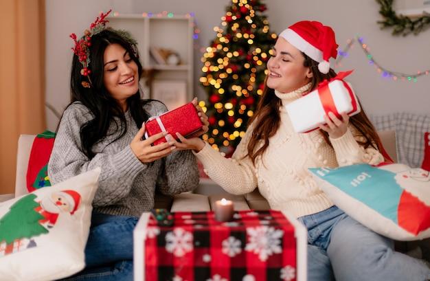 Tevreden mooie jonge meisjes met kerstmuts en hulstkrans houden en kijken naar geschenkdozen zittend op fauteuils en genieten van kersttijd thuis Gratis Foto