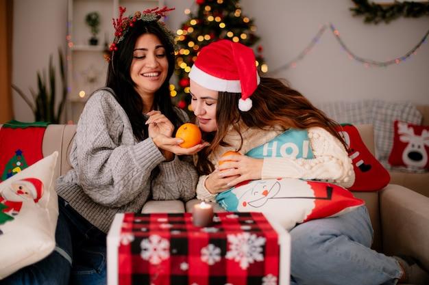 Tevreden mooie jonge meisjes met kerstmuts houden en sinaasappelen snuiven zittend op fauteuils en genieten van kersttijd thuis Gratis Foto