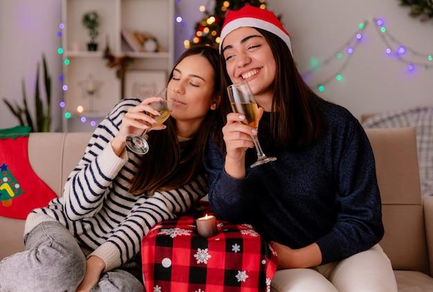 Tevreden mooie jonge meisjes met kerstmuts houden glazen champagne zittend op fauteuils en genieten van kersttijd thuis Gratis Foto