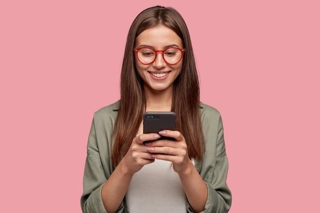 Tevreden mooie vrouw houdt moderne mobiele telefoon Gratis Foto