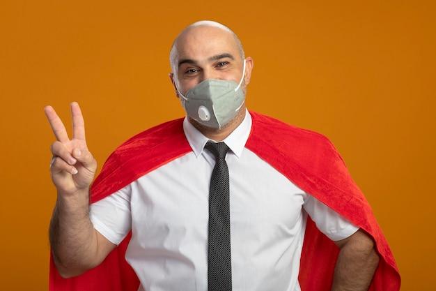 Tevreden superheldzakenman in beschermend gezichtsmasker en rode cape die v-teken tonen Gratis Foto