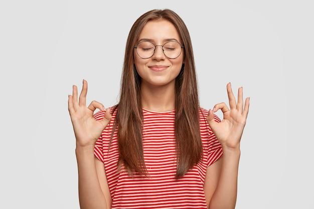 Tevreden tevreden jong vrouwelijk model maakt nul gebaar, draagt een transparante bril, heeft lang donker haar Gratis Foto