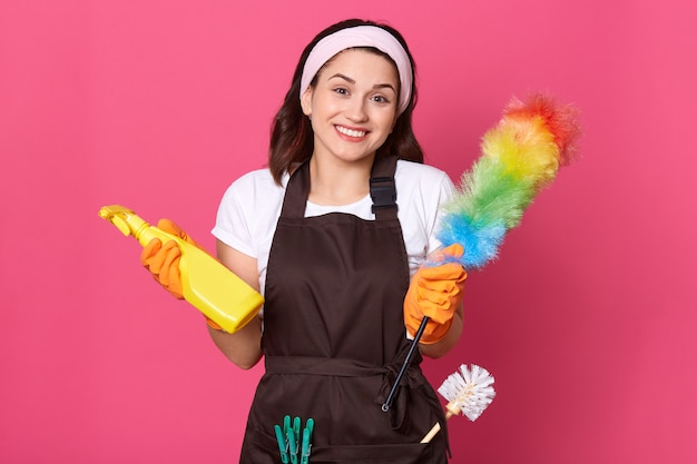 Tevreden vrouw gekleed in casual t-shirt, schort en haarband, houdt wasmiddel en pp-stofdoek vast Gratis Foto