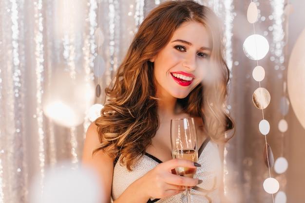 Tevreden vrouw in feestelijke outfit met glimlach. momentopname van krullend meisje champagne drinken Gratis Foto