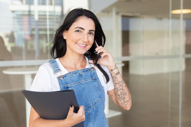 Tevreden vrouw met omslag die door smartphone spreekt Gratis Foto