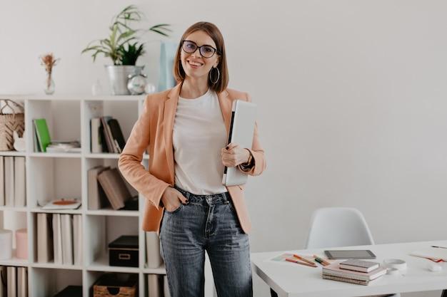 Tevreden vrouwelijke ondernemer poseren met laptop in de hand tegen van haar minimalistische kantoor. Gratis Foto