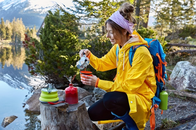 Tevreden vrouwelijke reiziger giet koffie uit koffiezetapparaat in theekopje, gebruikt rode camping butaanfles, draagt regenjas met rugzak Gratis Foto