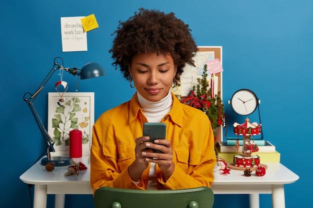 Tevreden vrouwelijke student neemt pauze van autodidact, gebruikt mobiel om online te chatten, bladert door applicatie, stuurt sms, controleert mail via wifi, zit op stoel bij werkplek, blauwe muur. Gratis Foto