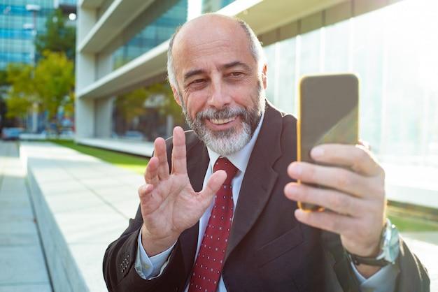 Tevreden zakenman golvende hand tijdens videochat Gratis Foto
