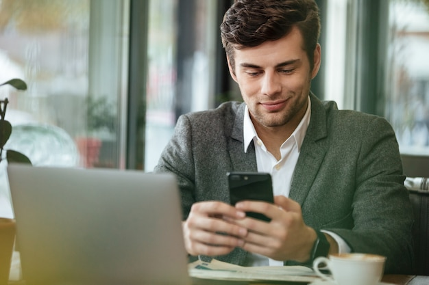Tevreden zakenmanzitting door de lijst in koffie met laptop computer terwijl het gebruiken van smartphone Gratis Foto