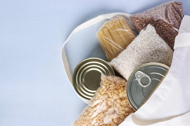 Textiel boodschappentas met voedsellevering op lichtblauw oppervlak. rijst, boekweit, pasta, ingeblikt voedsel. levering van voedsel, donatie, ruimte voor tekst Premium Foto