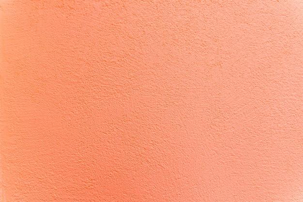 Textuur, muur, beton, levende koraalkleur. muurfragment met krassen en scheuren. decoratieve oude stucwerk muur, gips. Premium Foto