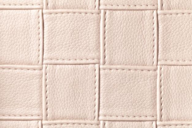 Textuur van beige leerachtergrond met vierkant patroon en steek, macro. samenvatting van modern decoratief lichtbruin textiel met geometrische vorm. Premium Foto