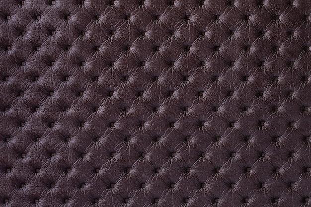 Textuur van donkerbruine leerachtergrond met capitonepatroon, macro. paars textiel in retro chesterfield-stijl. Premium Foto