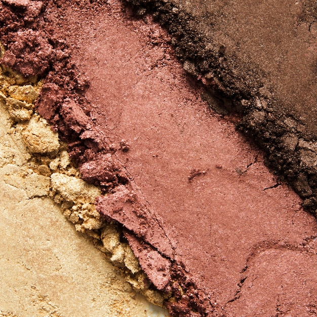 Textuur van gebroken oogschaduw of poeder. het concept van mode- en schoonheidsindustrie. detailopname. Premium Foto