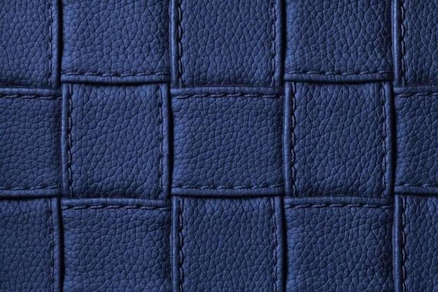 Textuur van marineblauwe leerachtergrond met vierkant patroon en steek, macro. samenvatting van modern decoratief donker indigotextiel met geometrische vorm. Premium Foto