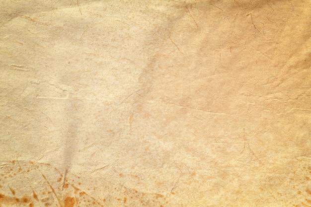 Textuur van oud beige papier met koffievlek, verfrommeld achtergrond. vintage bruine grunge oppervlak achtergrond. Premium Foto