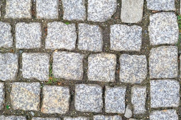 Textuur van oud cobbled-bestratingsclose-up. abstracte granietachtergrond. Premium Foto