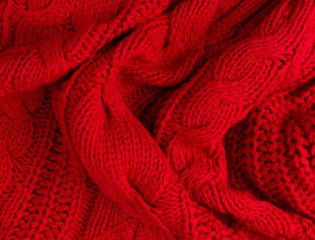 Textuur van rode gebreide stof dicht omhoog. wollen gebreide kleding Premium Foto