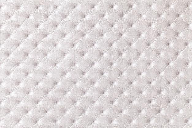 Textuur van witte leerachtergrond met capitone patroon, macro. parelmoer textiel in retro chesterfield stijl. vintage stof. Premium Foto