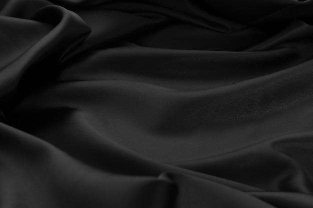 Textuur zwart satijn rimpel stoffen doek oppervlak gebruikte ons luxe achtergrondproducten ontwerpen Premium Foto