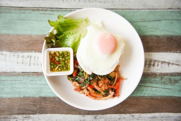 Thais eten pittig gebakken recept met groenten en chili saus. rijst gegarneerd met gewokte varkensrundvlees met heilige basilicum en gebakken ei Premium Foto