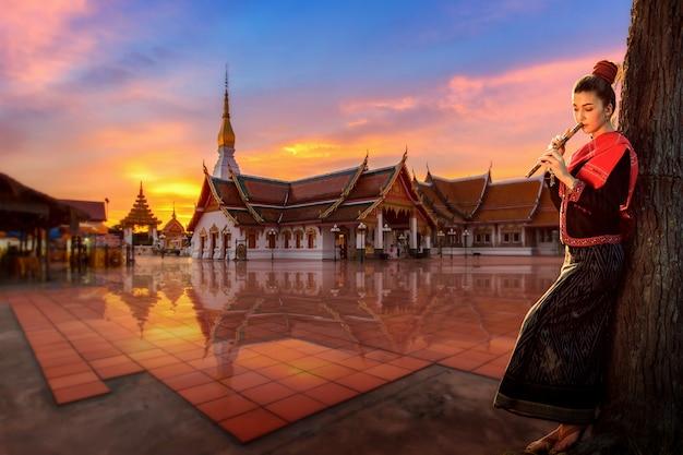 Thais meisje in een nationale kleding die zich aan de thaise fluit bevinden op boeddhistisch tempelgebied, sakonnakhon, thailand. Premium Foto