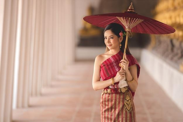 Thais meisje in traditioneel thais kostuum met rode paraplu in thaise tempel, identiteitscultuur van thailand. Premium Foto